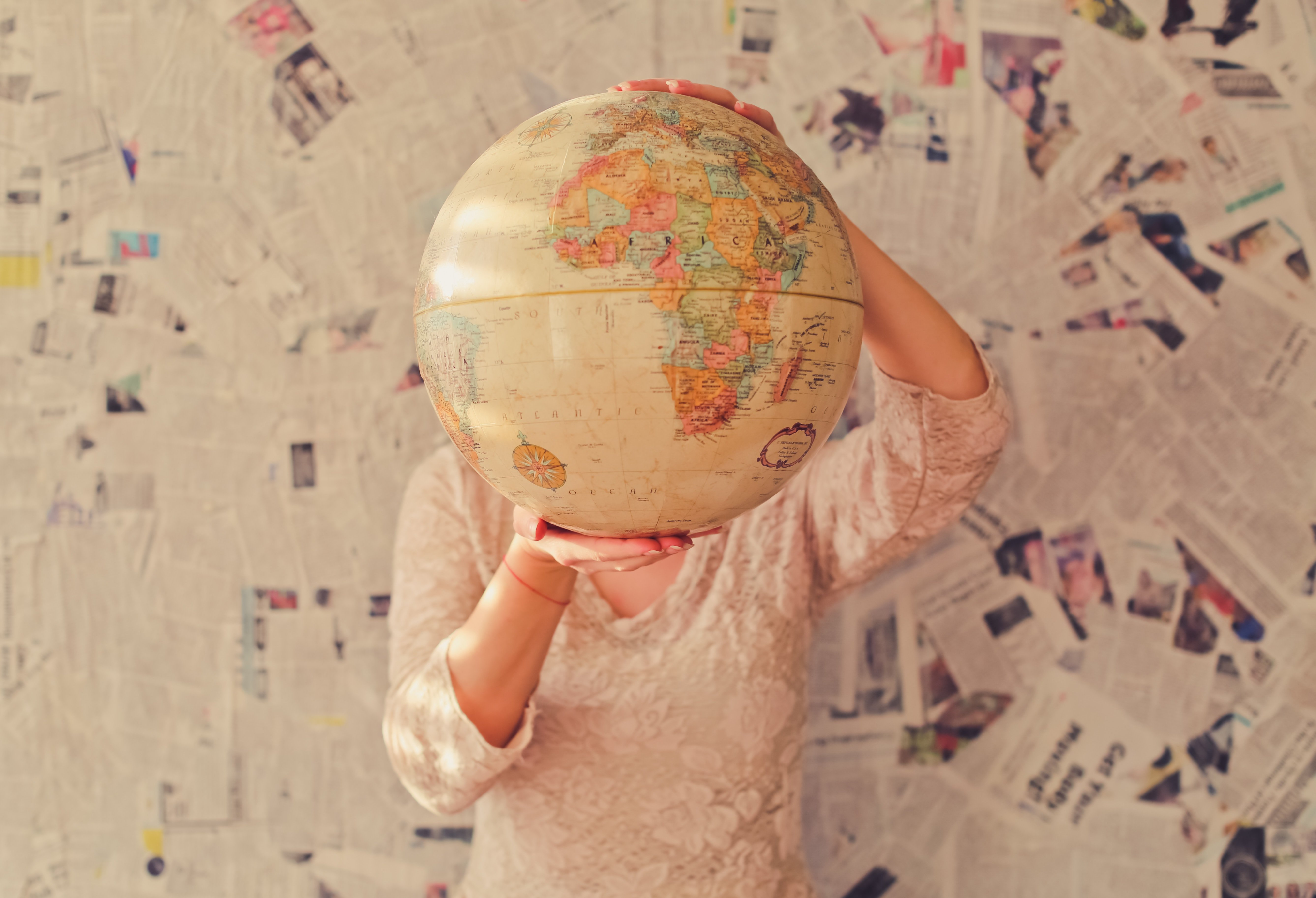 A woman holding up a globe, showing the various options of countries for teaching english abroad.